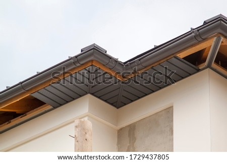 close-up view of a house with a gray roof and plums and filing of roof overhangs with soffits of house under construction Stock photo ©