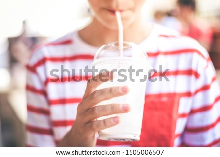 Close Up view of a kid drinking a milkshake at the bar. Colorful no face portrait of young boy holding a glass with a fresh beverage. Teen sucks a cold drink with a straw. Greedy, gluttonous concept.