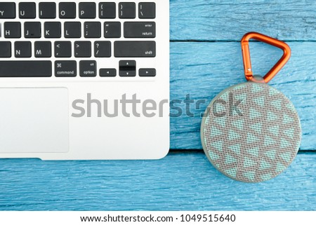 Close-up view of a Laptop and Bluetooth speaker color Gray and blue rechargeable batteries and built-in amplifier for playback music. Wireless speaker On the blue wooden floor
