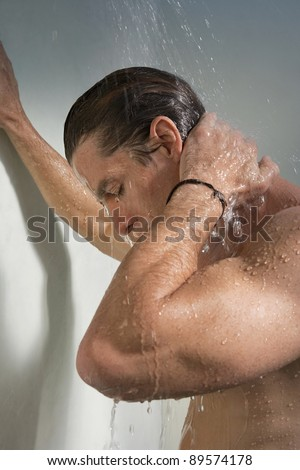 Close up view of a man having a shower and leaning on the wall.