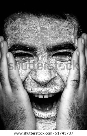 Close up view of a man\'s hands on the face covered in flour, screaming.