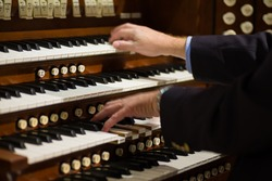 Close up view of a organist playing a pipe organ with motion blur.