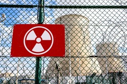 Close-up view of a radioactivity warning sign on the security fence with barbed wire of a nuclear power station with two cooling towers in a blurry background.