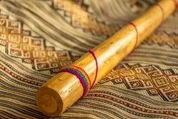 Close up view of a rain stick on a Peruvian textile. Natural light. Andean music concept.