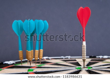 Close-up view of a red dart on the bullseye fand a group of blue darts all together in the background ストックフォト ©