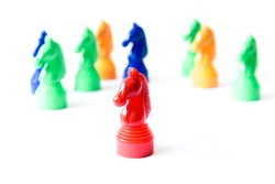 Close up view of a red horse is following by other ones in a horse race (board game) isolated on white. Concept of leadership, teamwork, business strategy, and influence. Stand out from crowd abstract