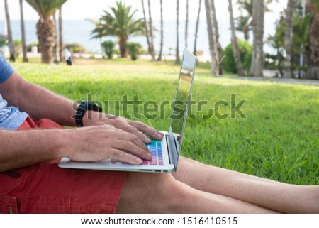 Close-up view of a senior man working outdoor with laptop. Sitting in a green meadow with palm trees and ocean in background. #1516410515