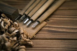 Close-up view of a set of wood chisels for carving wood, sculpture tools on the wooden background surrounded by wooden chips. High-quality photo