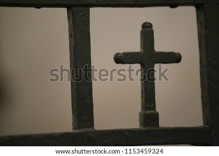 Close up view of a small metallic cross incorporated in a black forged gate. Religious sign located in a french church. Silhouette of a catholic symbol. Blur brown background. Abstract picture.