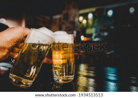 Close-up view of a two glass of beer in hand. Beer glasses clinking in bar or pub Stok fotoğraf ©