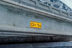 Close up view of a vertical clearance sign at the side of a concrete bridge