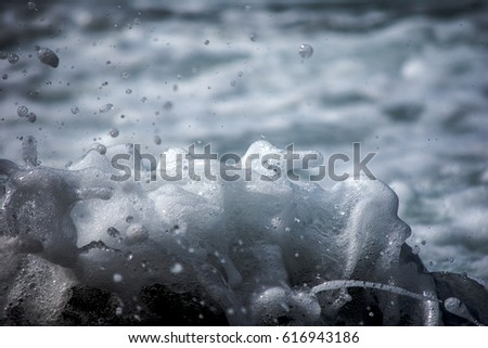 Close up view of a wave splashing on a rock. #616943186