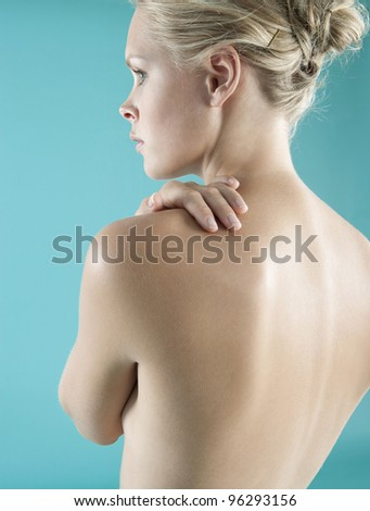 Close up view of a woman's bare back with her hand on her shoulder.
