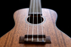 Close up view of a wooden ukulele body isolated on a black background.
