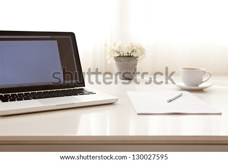Close up view of a work desk interior with a laptop computer, a cup of coffee and white curtains on a sunny day.