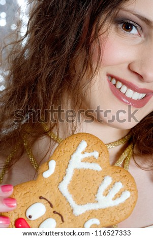 Close up view of a young woman holding a Christmas rain deer biscuit with a silver sequins background.