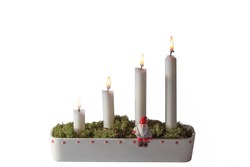 Close up view of advent candlestick decorated with little figure of Santa Clause and green moss.