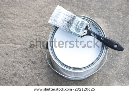 Close-up view of aluminum paint can on concrete with white paint and dirty paint brush, shallow DOF