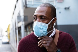 Close up view of an African American man wearing red pullover, out and about in the city streets during the day, putting on a face mask against air pollution and covid19 coronavirus.