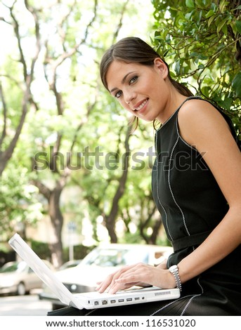 Close up view of an attractive businesswoman using a laptop computer while sitting in a leafy city street during a sunny day, smiling.