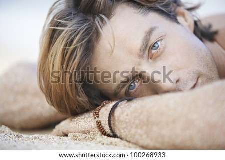 Close up view of an attractive young man laying down on a white sand beach.