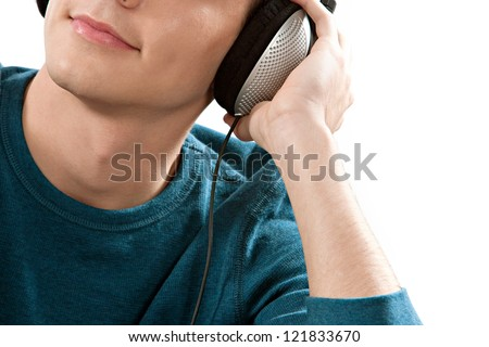 Close up view of an attractive young man's half face listening to music with his headphones against a white background.