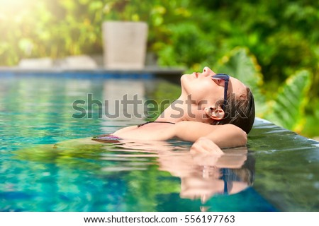 Close up view of an attractive young woman relaxing on a spa's swimming pool.Travel, happiness emotion, summer holiday concept. stock photo