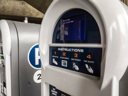 Close up view of an electronic pay-to-park machine inside a parking garage near a university