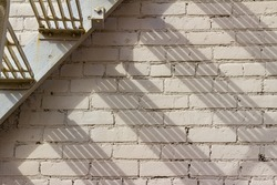 Close up view of an industrial looking gray metal fire escape stairway in front of a painted brick wall building, with shadows from low angle sunlight