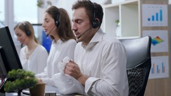 Close up view of angry and nervous call center operator with headset talking with the hotline customer, being irritated, uses bubble wrap to calm down and continues conversation. Stressful situation