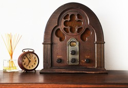 Close up view of antique wooden radio and broken clock with white wall in background