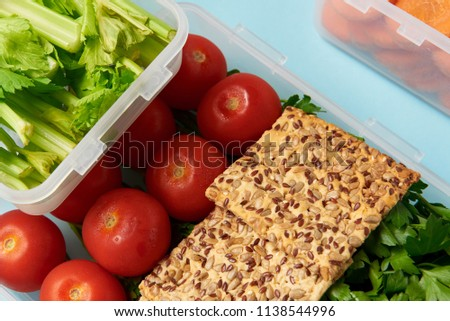 close up view of arrangement of food containers with fresh vegetables and cookies isolated on blue