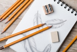 Close-up view of artist's or designer's table. Pencils, sharpner and eraser laying on sketch book with hand-drawn feathers