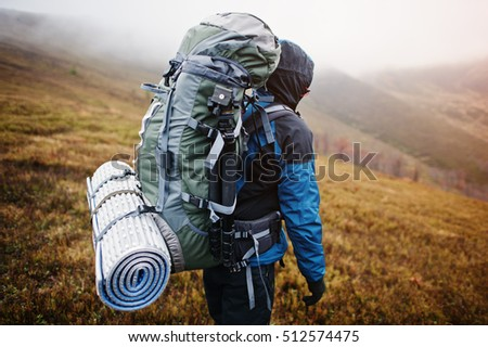 Close up view of back tourist backpack mats and tripod, wearing on blue tourism jacket with a hood and standing on mountain