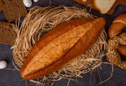 close-up view of baguette on straw surface with different breads and eggs on maroon background