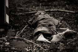 Close up view of bare feet of dead body sticking out of bag or rug, thrown in woods