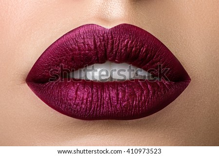 Close up view of beautiful woman lips with purple matt lipstick. Open mouth with white teeth. Cosmetology, drugstore or fashion makeup concept. Beauty studio shot. Passionate kiss