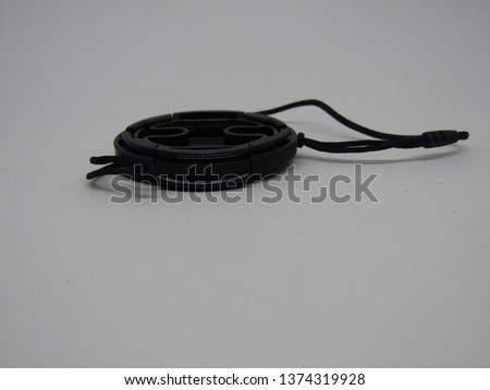 Close up view of black lens cap camera prosumer dslr with strap isolated on white background. Side view equipment  professional concept