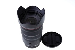 Close up view of black modern lens and lens cap isolated on white background.