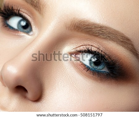 Stock Photo Close up view of blue woman eye with beautiful golden shades and black eyeliner makeup. Classic make up. Perfect brows. Studio shot