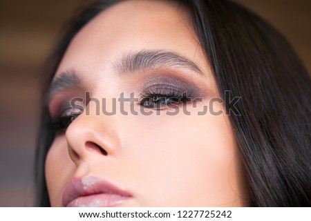 Close up view of blue woman eye with beautiful shades and black eyeliner makeup. Classic make up. Perfect brows. Studio shot