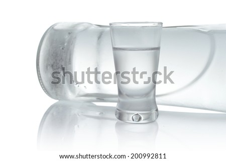 Close-up view of bottle lying and glass of vodka isolated on white