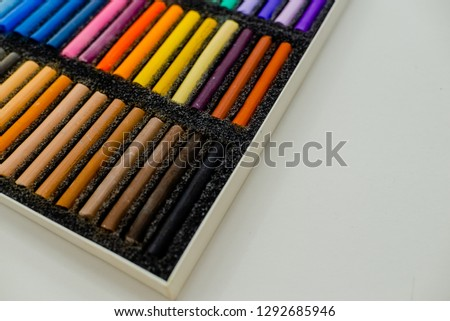 Close up view of bright colorful pastel chalks  on white background. Set of multicolored pastel crayons in openartist box on a white background, top view. #1292685946