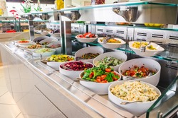 close up view of buffet table with different salads  in big white plates. hotel dinning room . all inclusive concept .