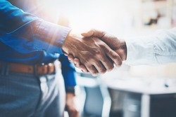 Close up view of business partnership handshake.Concept two businessman handshaking process.Successful deal after great meeting.Horizontal,flare effect, blurred background