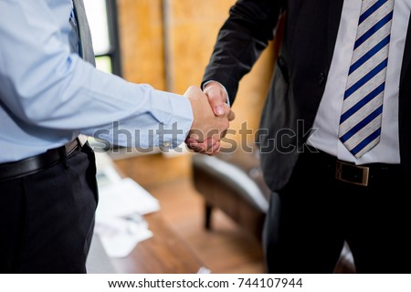 Close up view of business partnership handshake,  two businessman handshaking process, co-working team on new startup project