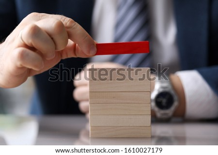 Close-up view of businessman holding one red cube and putting on tower of light wooden blocks. Selective focus on bars. Leadership and uniqueness concept