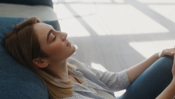 Close up view of calm young woman having healthy daytime nap dozing relaxing on couch with eyes closed hands behind head peaceful girl sleep breathing fresh air resting leans on comfortable sofa home