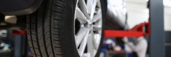 Close-up view of car all-season tire with aluminum rim. Mechanical lift for vehicle. Automobile service center or workshop concept. Professional auto maintenance