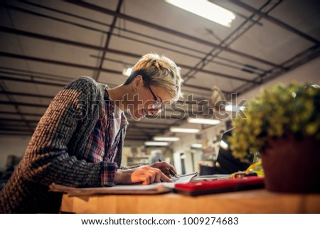 Close up view of charming smiling motivated short hair attractive middle aged industrial female engineer with eyeglasses working with blueprints and laptop in the workshop. - Shutterstock ID 1009274683